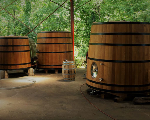 Near a bright summer forest, three foeders sit in an open air warehouse
